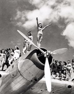 1939-1940 New York World's Fair - the Aquabelles, a group of swimming performers, and U.S. Army Air Corps officers pose on the wing and streamlined engine nacelle of the Boeing XB-15 long-range bomber