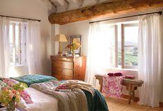 Dormitorio rústico con viga vista y banqueta bajo la ventana