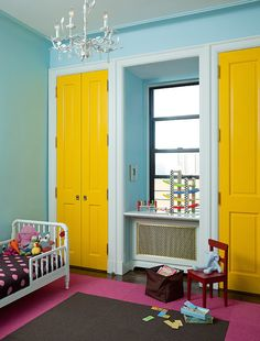 Contemporary kid's room features blue walls framing yellow bi-fold doors flanking window over grill front radiator cover alongside a white vintage bed dressed in pink and brown bedding atop fuchsia and brown carpet tiles illuminated by white tole chandelier.