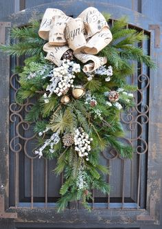 Rustic French winter holiday swag, burlap cream frost berry,mixed greens, aged jingle bells.. $165.00, via Etsy.