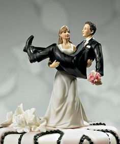 """""""To Have And To Hold"""" Wedding Cake Topper made of hand painted porcelain.  The bride is using her strength to carry her groom over the threshold. The bride is wearing a traditional, elegant white dress and a matching headband. The groom is wearing a handsome black suit and he is holding the bride's bouquet."""