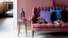peinture rose, canapé en tissu capitonné assorti, et coussins décoratifs en bleu et violet