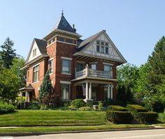 Large 3 story red brick Victorian home with white pillars in front supporting second story front deck