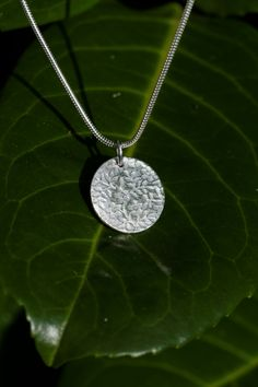 Round Floral Necklace by Saulberry A simple, elegant round pendant with a subtle floral texture. Made from fine silver and a sterling silver chain.
