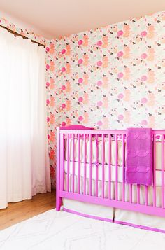 Pink crib and flower wallpaper in little girls room