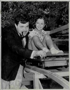 Shirley Temple with Orson Welles, riding a mini-roller coaster in the garden, late 1930s.