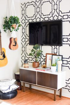 The wall opposite the sofa houses the TV and musical instruments.
