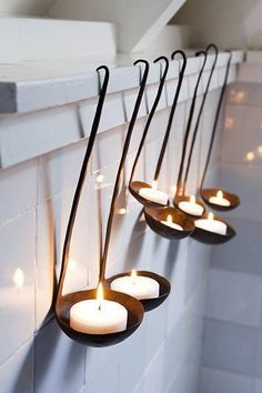 Old thrift shop or antique ladles tilted up to hold tea light candles. Would look great on rustic fireplace or in the bathroom. Could use a nice curtain rod to hang them mid-wall. Would also look great painted!!