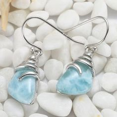 The Larimar Silver Swirl Drop Earring features two triangular Larimar stones swirled at the top by a ribbon of silver that goes up into the hook at the earlobe. Stunning blues and whites in the stones