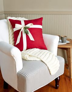 Take a plain pillow from ho-hum to ho-ho-ho by simply wrapping it like a present. (Yes, it's that simple.) Add a sprig of greenery or a festive ornament for an extra bit of flourish.  decorative pillows, $14; satin ribbon, $11