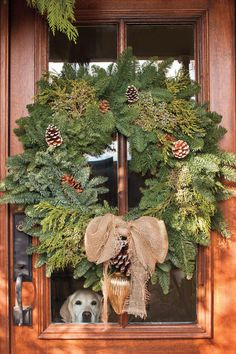 Rustic yet Redefined - Deck the Paws - Southernliving. The windows in this beautiful wood door provide an ideal spot for this pup to look out for arriving guests. A generous wreath of cedar, juniper, and noble fir embellished with pinecones in various sizes brings nature right to the doorstep. A burlap bow adds a bit of homespun flair, and the vintage mercury glass ornament below gives the look an elegant air.