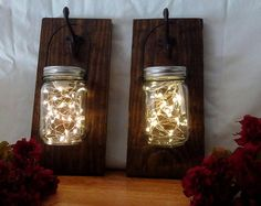 Here is a pair of mason jar lanterns. The warm dark stain adds a rustic charm to any room. The hooks are reproduction cast iron. The mason jars are pint size and contain fairy lights (included). The handle is made from black metal. Add a rustic charm to your home with these