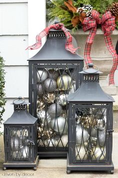 A trio of lantern filled with inexpensive silver and gold ornaments from HomeGoods for simple, beautiful front porch holiday decorations (sponsored pin)