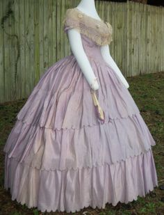 Lilac silk ballgown, circa 1860, shown with an original bertha (a wide deep cape like collar, often of lace, usually to cover up a low neckline) and fan.