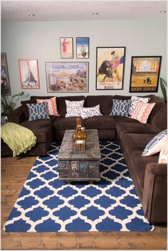 Brown sectional with bright throw pillows. Bright accent rug. I don't care for the choice of art on the back wall. I would incorporate a canvas mural of tree with the kids names/hands on them in neutral color with pop of color