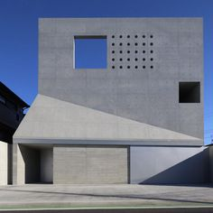 Square and circular holes puncture the concrete facade of this house in Japan
