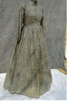 1860s Fashion - here is a homespun every-day dress owned by Vick Betts. Every-day dresses were often one piece, instead of bodice and skirt being separate, and the closure is in front.  Work dresses were of sturdy material, wool being the favorite as it was fire-retardant. Cotton was also used, however, as it was more easily washable.  Note once again the geometric designs in the fabric and the dropped shoulder seams. This hand-sewn dress is an enduring testimony to some lady's sewing abilit