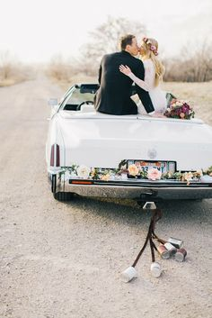 wedding flower garland and cans on a car | Barefoot BlondeBarefoot Blonde