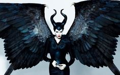 Maleficent - Angelina Jolie as the protagonist wearing a black long-sleeved dress with feathered bodice and her trademark horned headpiece, ...