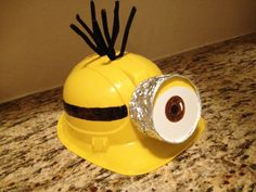 DIY minion hat for costume. Despicable me yellow minion. All you need is a construction hat, fuzzy sticks, black an brown sharpie, Aluminum foil, a solo cup and white presentation board.