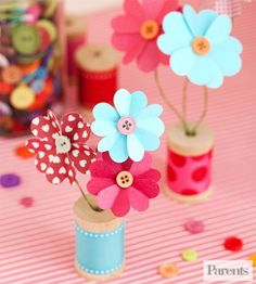 A simple wooden spool covered in ribbon holds a precious flower bouquet.                 See the next slide for instructions.