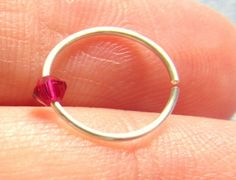 This is for a SINGLE hoop ring perfect for your upper ear, nose, eyebrow, or wherever else you have pierced! This is not a cuff, it is an actual piercing ring! The bead on it is a Ruby Swarovski Elements Bicone. It is loose, not glued, on the ring.  $6.25   #cartilagehoop, #birthstonejewelry, #birthstoneearring, #piercedearring #july, #ruby