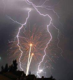 Lightening strikes during a fire work display.