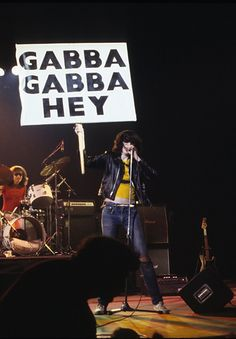 """Joey Ramone holds up a """"Gabba Gabba Hey"""" sign while performing with The Ramones"""