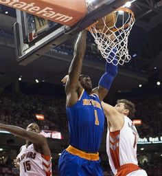 New York Knicks' Amare Stoudemire dunks on Toronto Raptors' Amir Johnson, left, and Andrea Bargnani during the first half of an NBA basketball game in Toronto on Friday, Feb. 22, 2013.