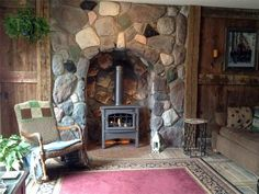 """This Old House — Reader Remodel Contest — Best Fireplace and Mantel Before and Afters 2013 — Rustic Stone Fireplace: After (Mary M. from Belmont, MI, writes: """". . . we tore out carpet and installed ceramic stone tile that looks just like barn-wood slats."""" [this can be seen between the rug and the front of the sofa, on the right side of the photo])"""