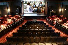 cine con asientos comunes en el centro y a los costados mesas y sillas simulando como una cafetería o restaurante