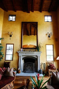 Placed over the stone fireplace, the large hand carved mirror is a beautiful Spanish style addition.