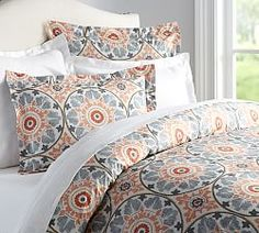 "Veronica Duvet Cover & Pillow Shams | Pottery Barn: Circular design coordinates with large Chat Noir print for over the bed. Also picks up the orange color. Gray feather design plush blanket and ""recycled"" sofa pillows in leaf like pattern with shades of gray and maroon accents."