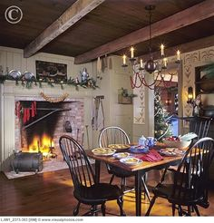Pine Bows and Apples dress the Mantle, Red Socks Hung from twine from the Hearth, Wood Paneling in Paint and Stenciled Walls, a  filled with Pine Sprigs, a Table of fresh baked pies is surrounded with Windsor Chairs, a Chandelier draped with a Cranberry Garland, and exposed ceiling beams.