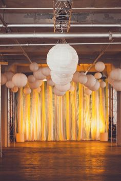 industrial indoor ceremony with paper lanterns and streamers // photo by AngelaReneePhoto.com