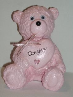 This beautiful pink teddy bear grave memorial, is painted in baby pink, with a little added glitter to make it sparkle, googly eyes and little black nose give it the cute factor.  With this pink teddy bear grave memorial holding a heart upon which the word Daughter will be in shining silver lettering. Finished off with a colour coordinated pink ribbon bow (ribbon designs may vary) and a plastic pink gem heart.