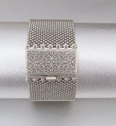 A silver beaded cuff made of seed beads and an intricate box clasp. This…