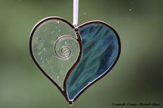 This beautiful heart suncatcher measures 3.75x3.5. I used a pale blue Spectrum waterglass and clear textured Spectrum glass. Added wire work gives this suncatcher a special touch. I hand cut and grind every glass piece and use the Tiffany Foil method to construct these suncatchers. A hook is soldered for hanging. These are framed in lead came and I have attached a ribbon for hanging.
