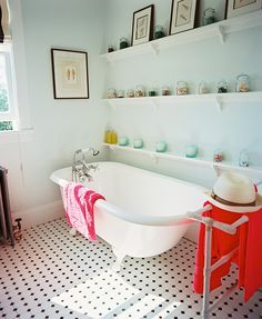 claw-foot tub next to jars of seashells and a patterned tile floor