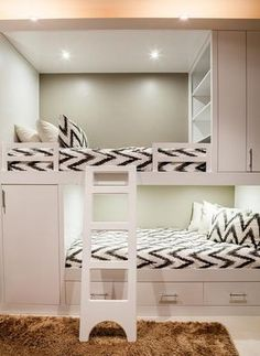 Contemporary bunk room features white built in bunk beds, with top bunk bed fitted with modular shelves, dressed in white and gray chevron bedding.