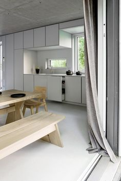 The minimalist kitchen and dining room in a contemporary Berlin house designed by three teams: Prenzlauer Berg architects (who created the structure), DesignYouGo, who devised the interior architecture, and Loft-Kolasinski, who supplied the custom and midcentury furnishings. Karolina-Bak-photo.