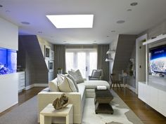 This gray and white living room is given a calm accent with blue in the large built-in fish tank. The area rug adds texture while also defining the seating area.  Gray textured wall covering