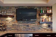 back splash of some sort, dark wood shelves, tv for bar area