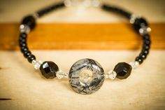 Closeup jewelry photography of a black bead bracelet with round gray stone.