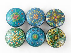 "These wood knobs are 1.5"" wide and have been painted black with a decoupage mandala pattern. Sealed with a triple coat gloss finish so these knobs are durable enough for everyday use on your cabinets or furniture. Mounting screws included, wood knobs feature a brass insert to ensure a secure fit when attaching the screws. Please note that these knobs are hand crafted so please expect slight variations in finish."
