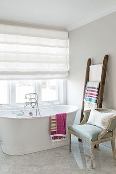 Instead of hiding your prettiest linens in a closet, put them on display via a wooden ladder. In an airy beach house, the upgraded towel bar stands within reach of a freestanding tub.    Shop a similar look: ladder, $50, amazon.com
