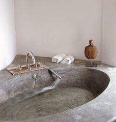 Destaque do ambiente, a banheira de cimento queimado chama a atenção e se destaca em meio às paredes brancas