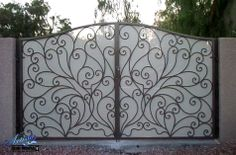 Scrolled wrought iron driveway gate with write perforated metal (privacy screen)