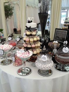 Elegant black and white themed wedding dessert table with a cupcake tower and a…