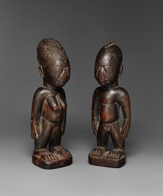 A PAIR OF IBEJI, MALE AND FEMALE  Nigeria, Probably from Egba  Pair of ibeji, from Egba, 22 cm high  22 cm. high  Each with smoothly worn facial features, the male with shaved head, the female with tall lobed coiffure, dark eroded patinas.